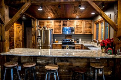 Gorgeous kitchen with huge granite bar, stainless appliances and reclaimed wood