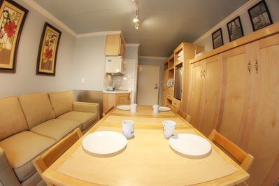 """Murphy bed in """"up"""" position with stowaway table and chairs on display."""