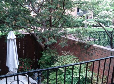 looking out from the private balcony to the fully enclosed brick patio (w/ grill