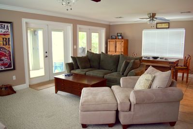 Living Room with two sets of French Doors that open onto a Lanai facing the lake