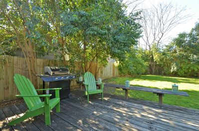 Yard - Gas grill and bench seating on the wooden patio.