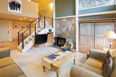 Rustic living room with couches and stone fireplace