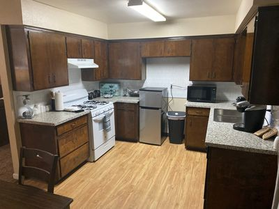 Kitchen with stove/oven, refrigerator, microwave, and dishwasher.