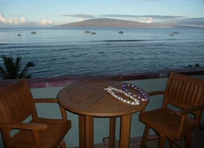 The huge lanai also features a large teak dining table and a teak seating area.