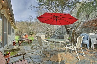 The patio is surrounded by boulders and shaded by a beautiful buckeye tree.