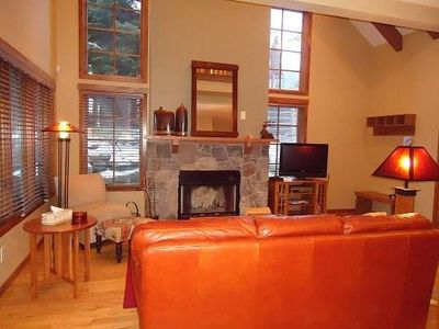 Orange leather couch facing stone fireplace and flat screen TV