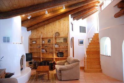 A warm, cozy woodburning fireplace in the spacious living room, firewood provide