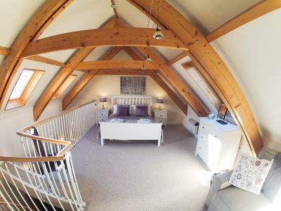 Light master bedroom with exposed beams, king size bed and double sofa bed