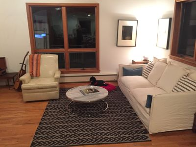 Spacious living room area with large comfy couch. (view at night, it is filled w