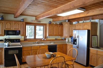 Fully equipped kitchen with granite counter tops. Two sets of patio doors