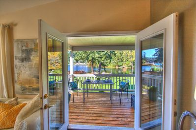 French doors from living room looking out towards deck, lawn and waterfront.