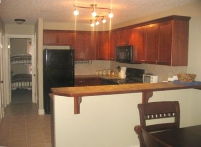 Beautifully stocked kitchen and glimpse of dining table and second bedroom