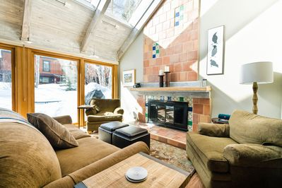 Main Living Room with gas fireplace, vaulted ceilings and natural light.