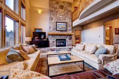 Clares in Town - Open concept living area with massive stone fireplace