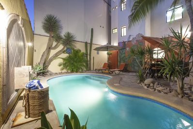The walled backyard is very private with its heatable pool, grill, and seating.