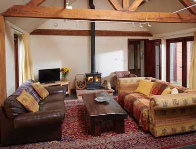 Cosy lounge at the Vine House with comfortable sofas and a toasty wood burner