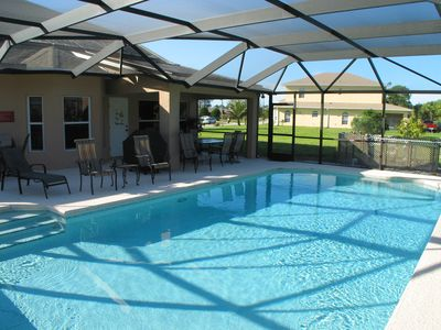 Shaded patio table and gas barbeque overlook the fully screened pool area.