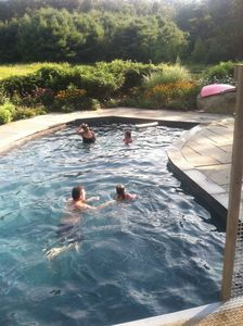 pool with family members photographed from deck & jump off ramp.