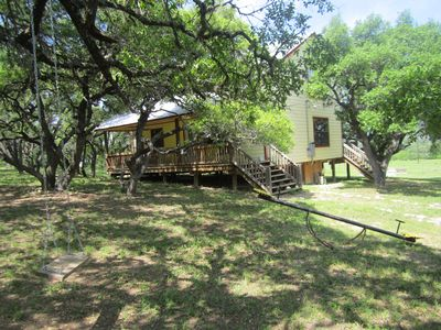 Front yard of Four Frio Sisters has teeter totter and swing to enjoy.