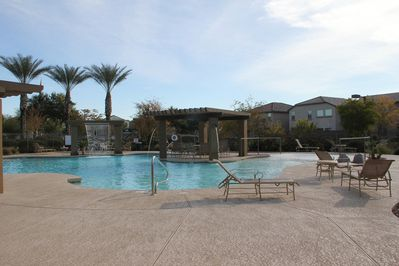 Community pool with water features, palm trees and hot tub.