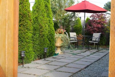 Fenced paved backyard with hot tub, fire pit and gas barbecue.