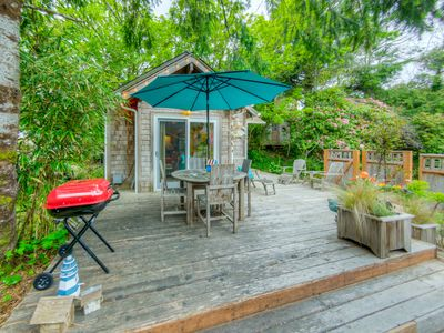 Front patio of Lil Love Shack with charcoal BBQ, table with umbrella and seating for four plus three other chairs and lounge chair, fire pit, and bench seat