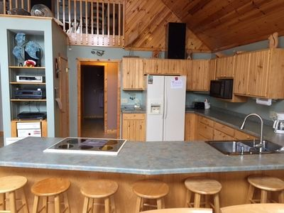 Kitchen w/ eating island.  Large food prep area. UPDATE stainless refrigerator
