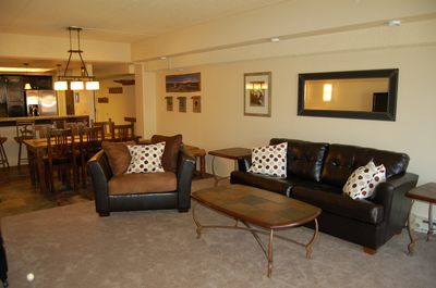 Relaxing family room features a queen leather sofa sleeper and overstuffed chair