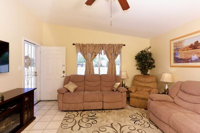 """The living area features 5 recliners facing a 50"""" TV"""