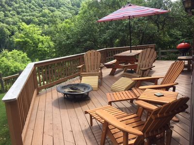 Deck w fire pit, chairs, picnic table and grill.