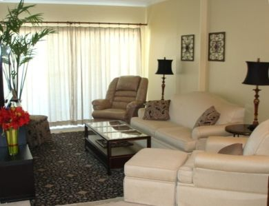 Living room w/comfy seating & sliders to balcony.