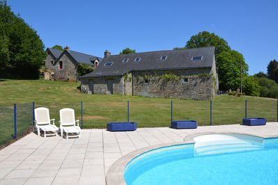 Fenced and heated pool is set in the garden away from the gites