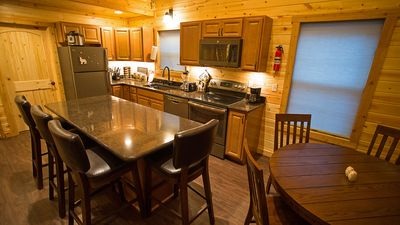 The kitchen features granite island and counters, and stainless appliances.