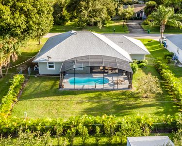Aerial picture of the private backyard featuring screened in & heated pool.