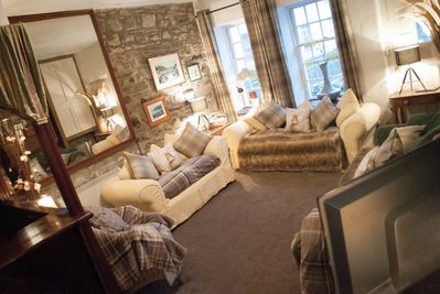 The sitting room, lots of throws cushions and flat screen TV, plus DVD and video