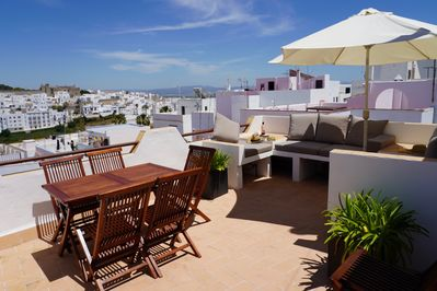 Spacious roof terrace with dining and lounging areas - both seating 5.