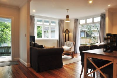 Sunny, light filled living room with french doors leading to deck.