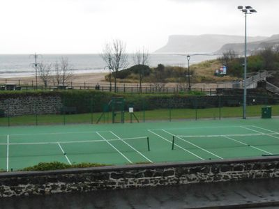view from balcony of tennis courts and seashore beyond