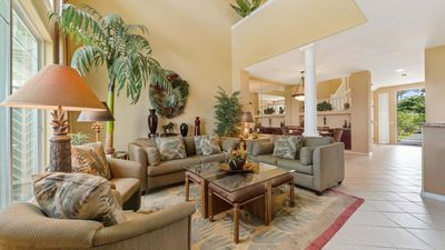 Modern open living room with tile flooring, Hawaiian inspired decor, and olive green couches