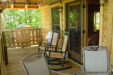 Lower level porch has dining table, rockers & swing