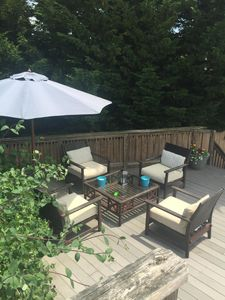 Outdoor seating under pine trees and umbrella on your own private deck