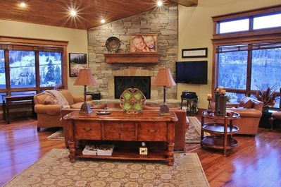 Cozy Main Level Living Room with Comfortable Seating, TV, and Warm Fireplace Surrounded by Mountain Views
