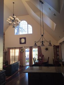 Great room with vaulted 20' ceiling,  multiple windows, and hardwood floors..