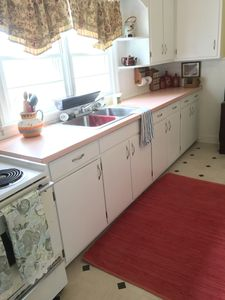 Well equipped kitchen with a stove, fridge, microwave and Keurig coffee pot.