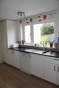 The kitchen with window overlooking the patio, BBQ and back garden