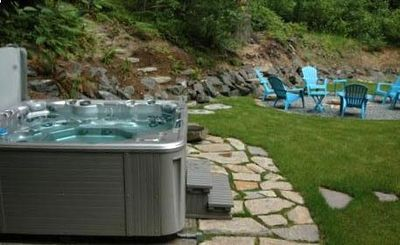 The hot tub and firepit in the backyard backed by National Forest