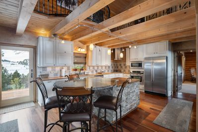 Fully stocked open concept kitchen with seating for 4 around the island.