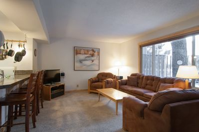 nice open plan living room with new blinds and big window looking into the back patio