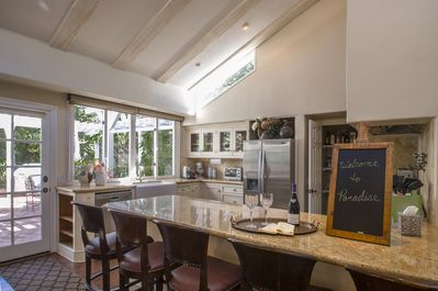 Gourmet kitchen with bar seating for 5 looks out on open floor plan. Hang time!