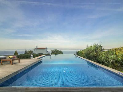 Photo for Modern 3 bed villa with infinity pool offering stunning views of the sea, within walking distance of the beach.